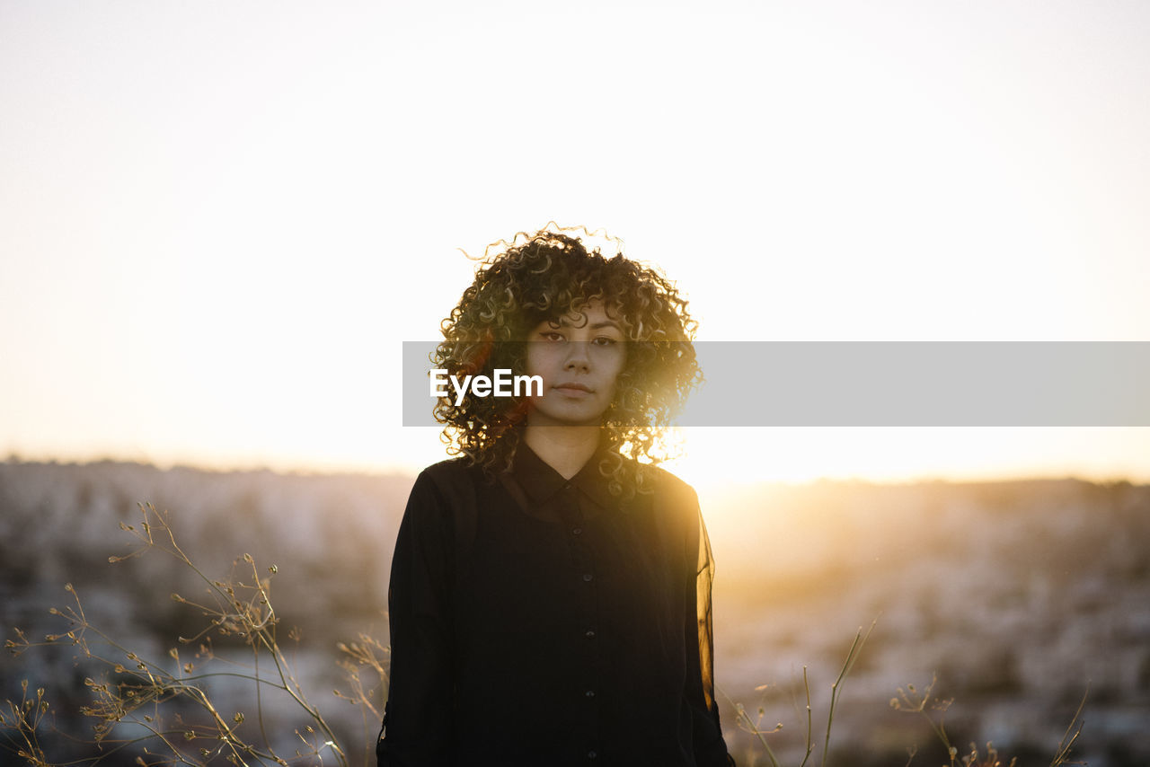 Portrait of woman standing on land against sky during sunset