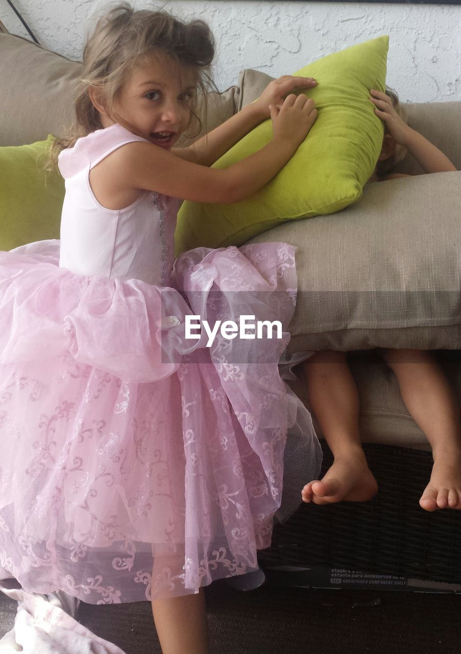 Siblings doing pillow fight at home