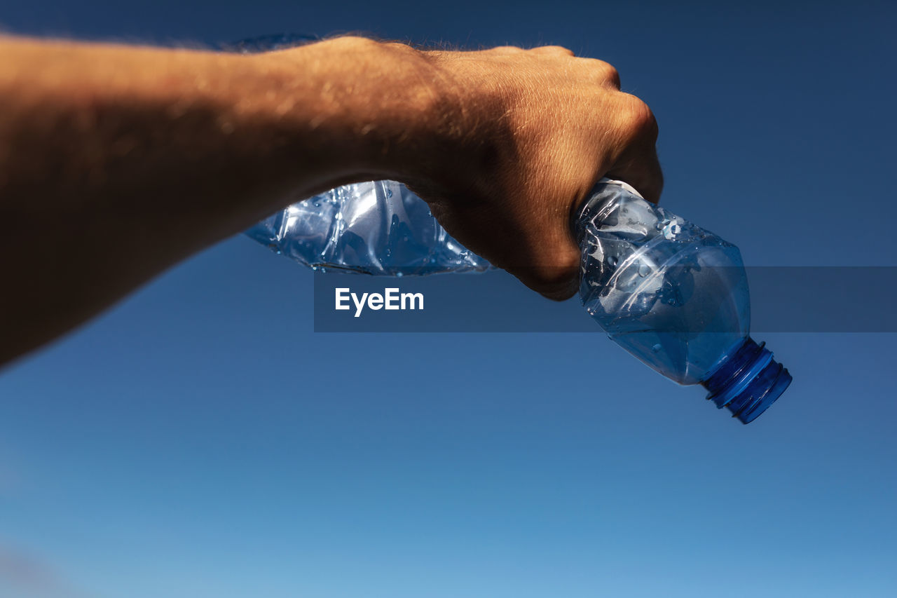 human body part, water, human hand, hand, sky, nature, body part, one person, holding, clear sky, close-up, blue, finger, men, human finger, real people, copy space, unrecognizable person, outdoors, glass, melting