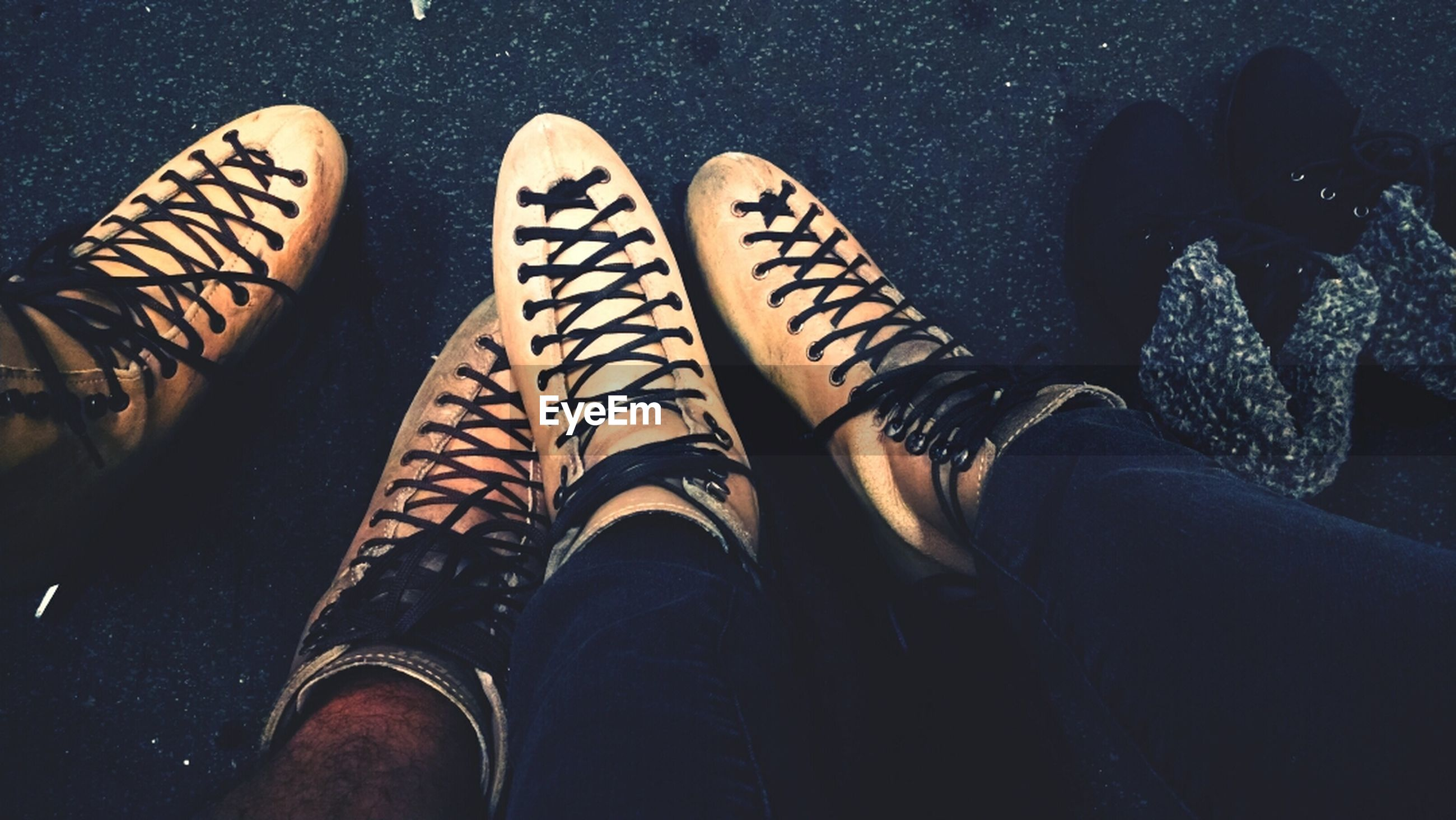 low section, person, shoe, personal perspective, lifestyles, human foot, men, leisure activity, footwear, standing, jeans, unrecognizable person, togetherness, high angle view, part of, canvas shoe