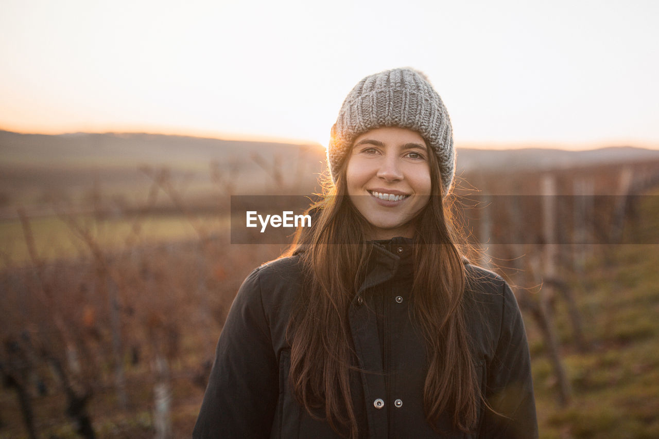 Portrait Of A Smiling Young Woman In Vineyard In Winter