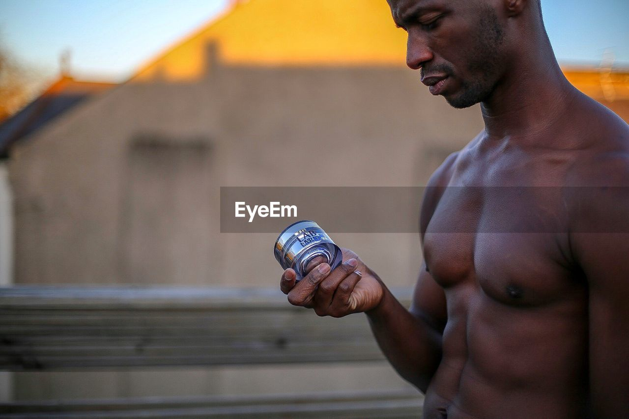 shirtless, lifestyles, exercising, strength, one person, muscular build, real people, outdoors, focus on foreground, sport, leisure activity, healthy lifestyle, young adult, building exterior, built structure, day, athlete, architecture, sky, sportsman, close-up, human hand