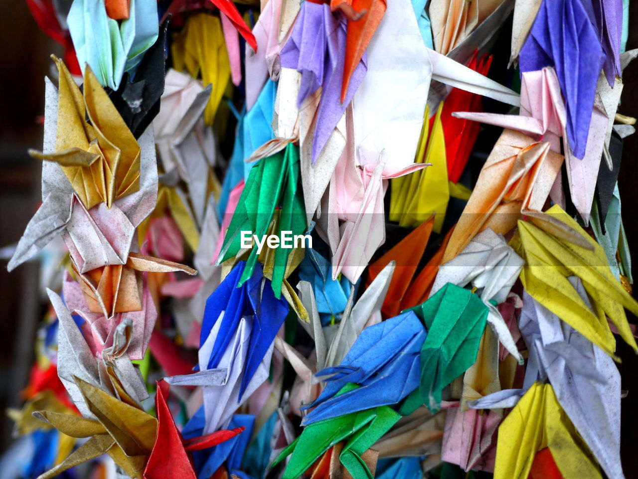 Colorful paper cranes hanging outdoors