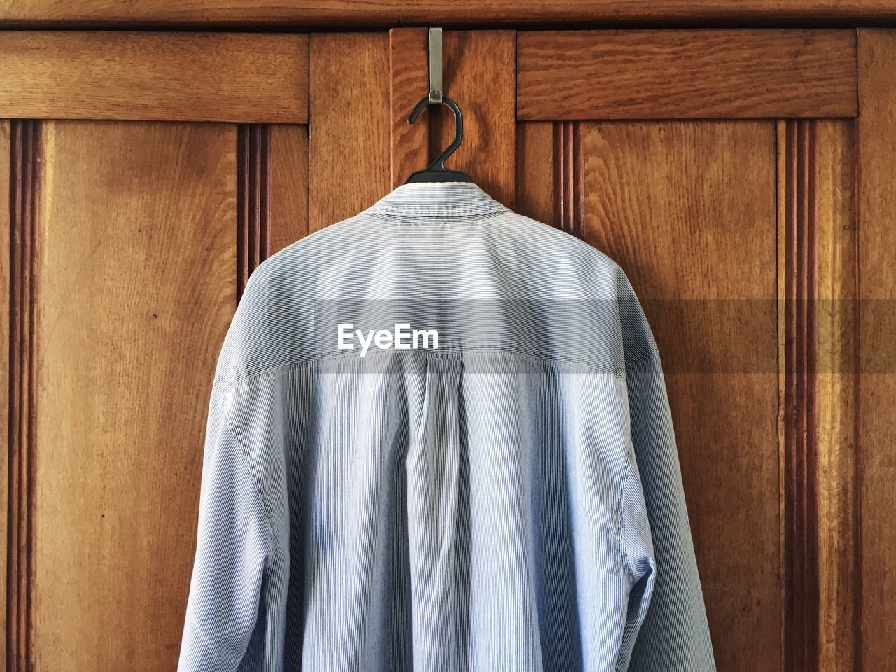 Gray Shirt On Coathanger Hanging From Wooden Cabinet