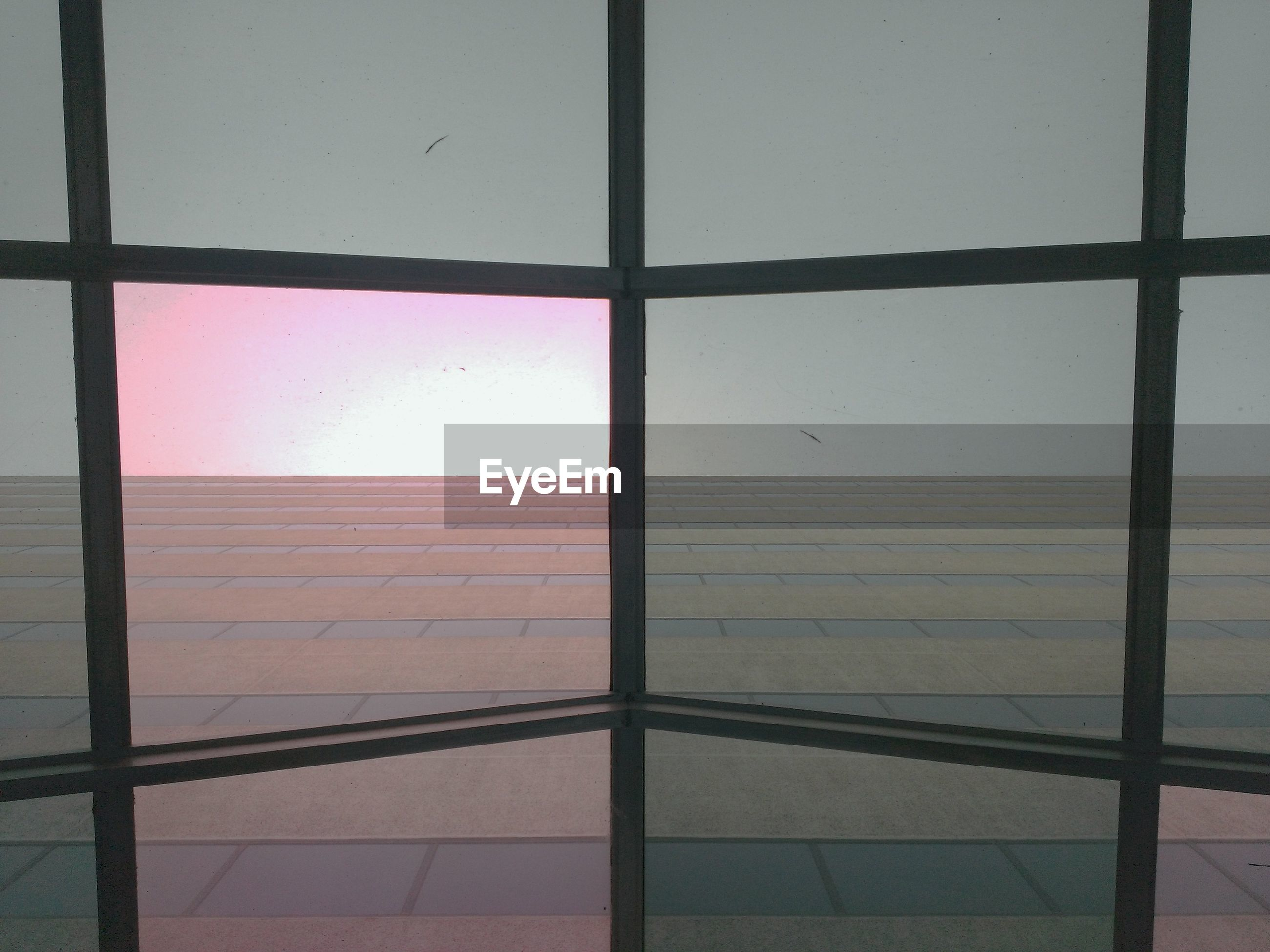 Low angle view of building against sky seen through skylight