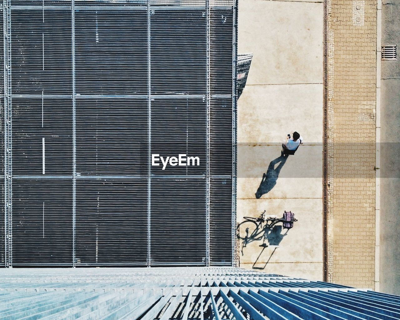 Overhead View Of Roof And Man Walking On Sidewalk