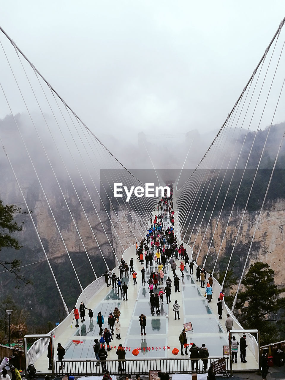 large group of people, suspension bridge, connection, sky, architecture, outdoors, bridge - man made structure, real people, built structure, travel destinations, day, men, people