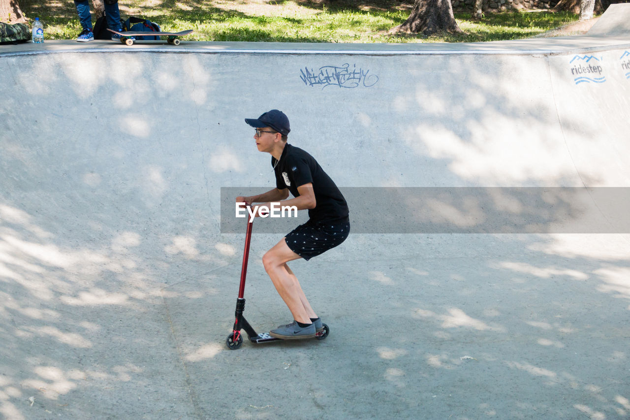 full length, real people, one person, casual clothing, leisure activity, lifestyles, day, nature, child, young adult, side view, transportation, sunlight, childhood, men, sport, outdoors, boys, riding, adolescence, teenager