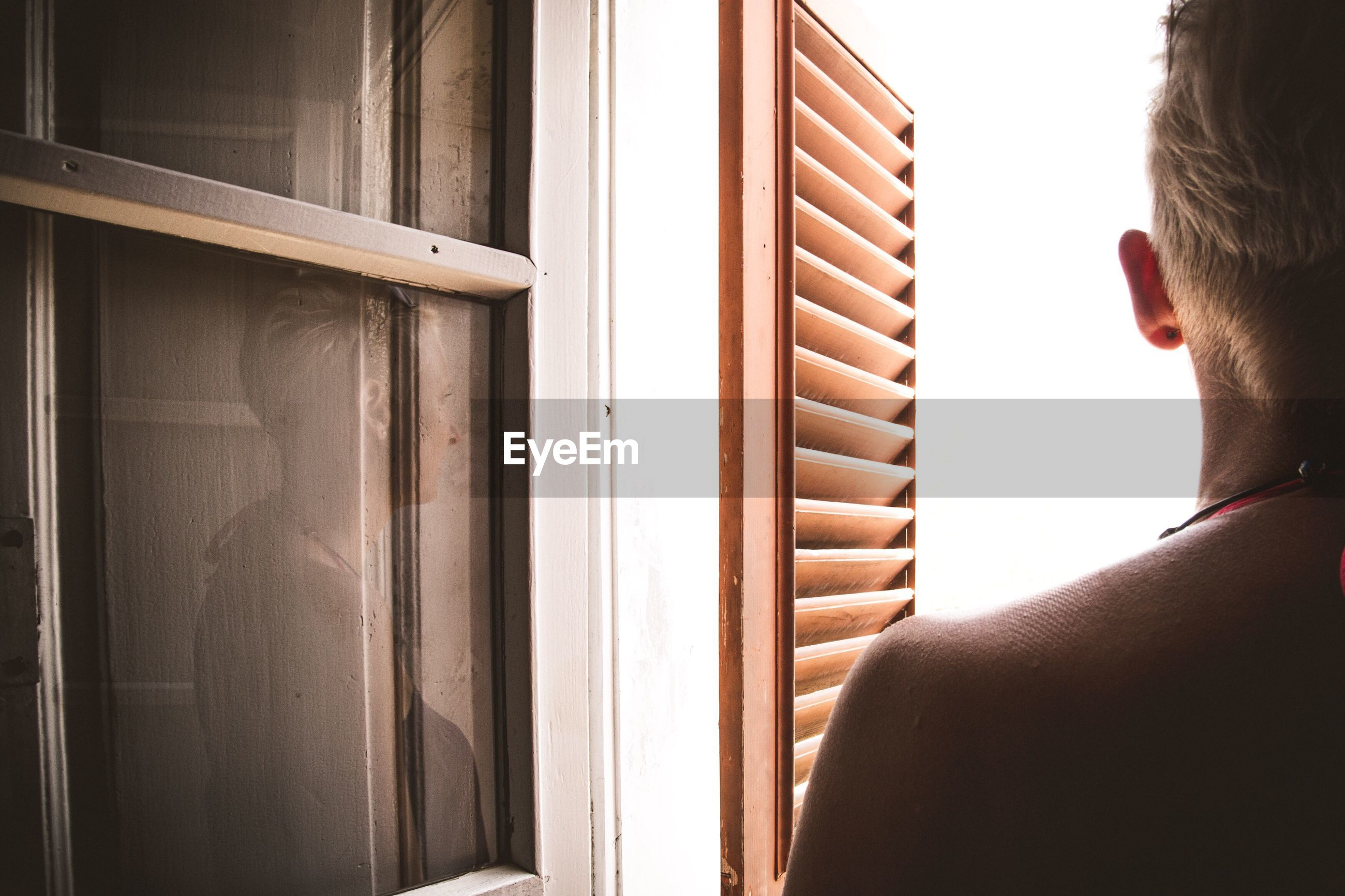 Cropped image of woman looking through window