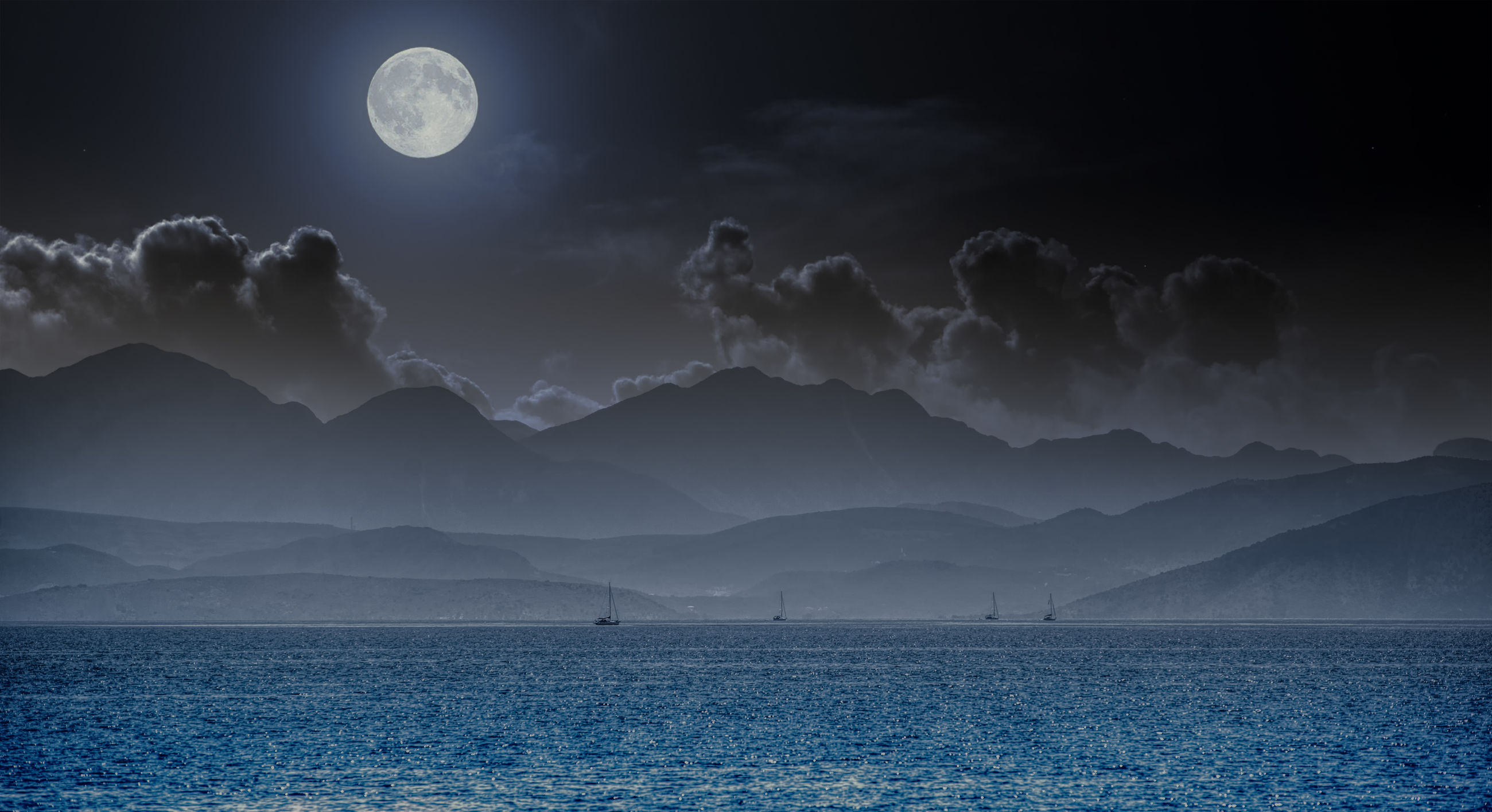 Scenic view of sea and mountains against sky at night
