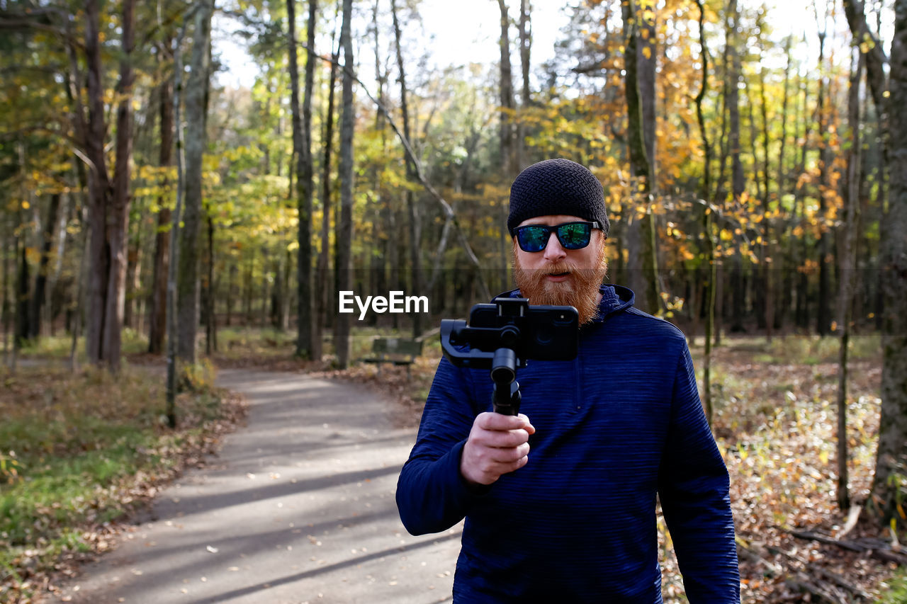 Man photographing while standing on footpath in forest