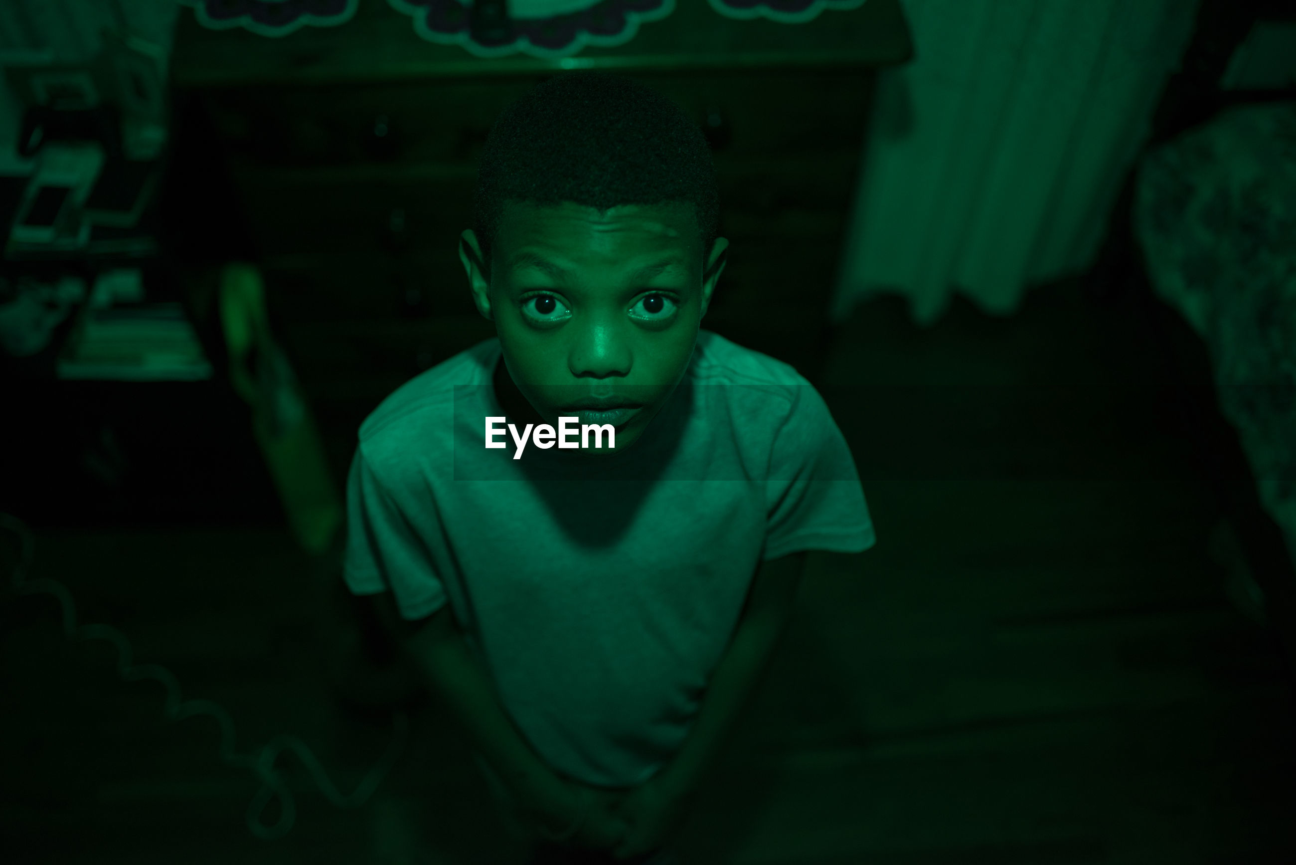 High angle portrait of boy standing in green illuminated room