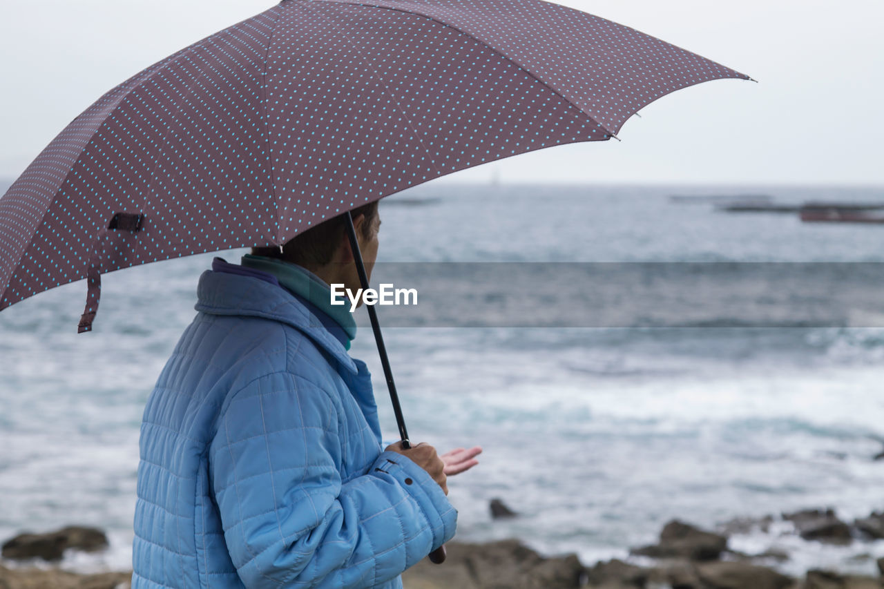 Woman in coat and umbrella in front of the coast