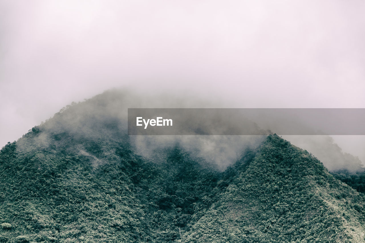 beauty in nature, mountain, scenics - nature, tranquility, fog, nature, tranquil scene, environment, no people, non-urban scene, sky, day, landscape, smoke - physical structure, outdoors, land, idyllic, remote, geology, mountain peak, power in nature