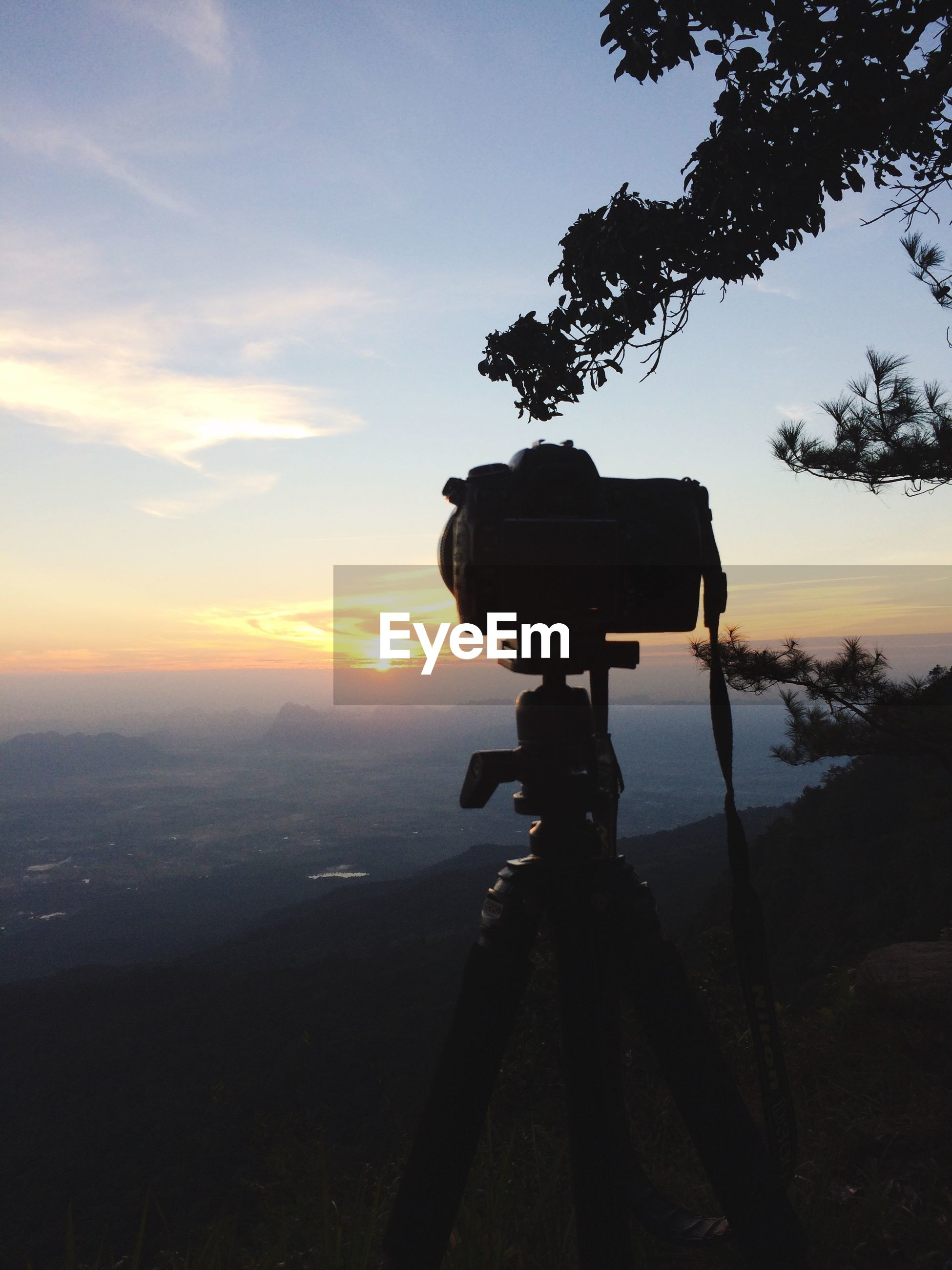 Close-up of dslr camera on tripod against sky during sunset
