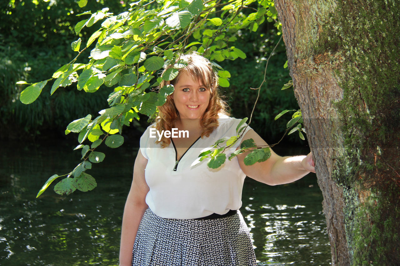 Portrait Of Smiling Woman Standing By Tree Against Lake