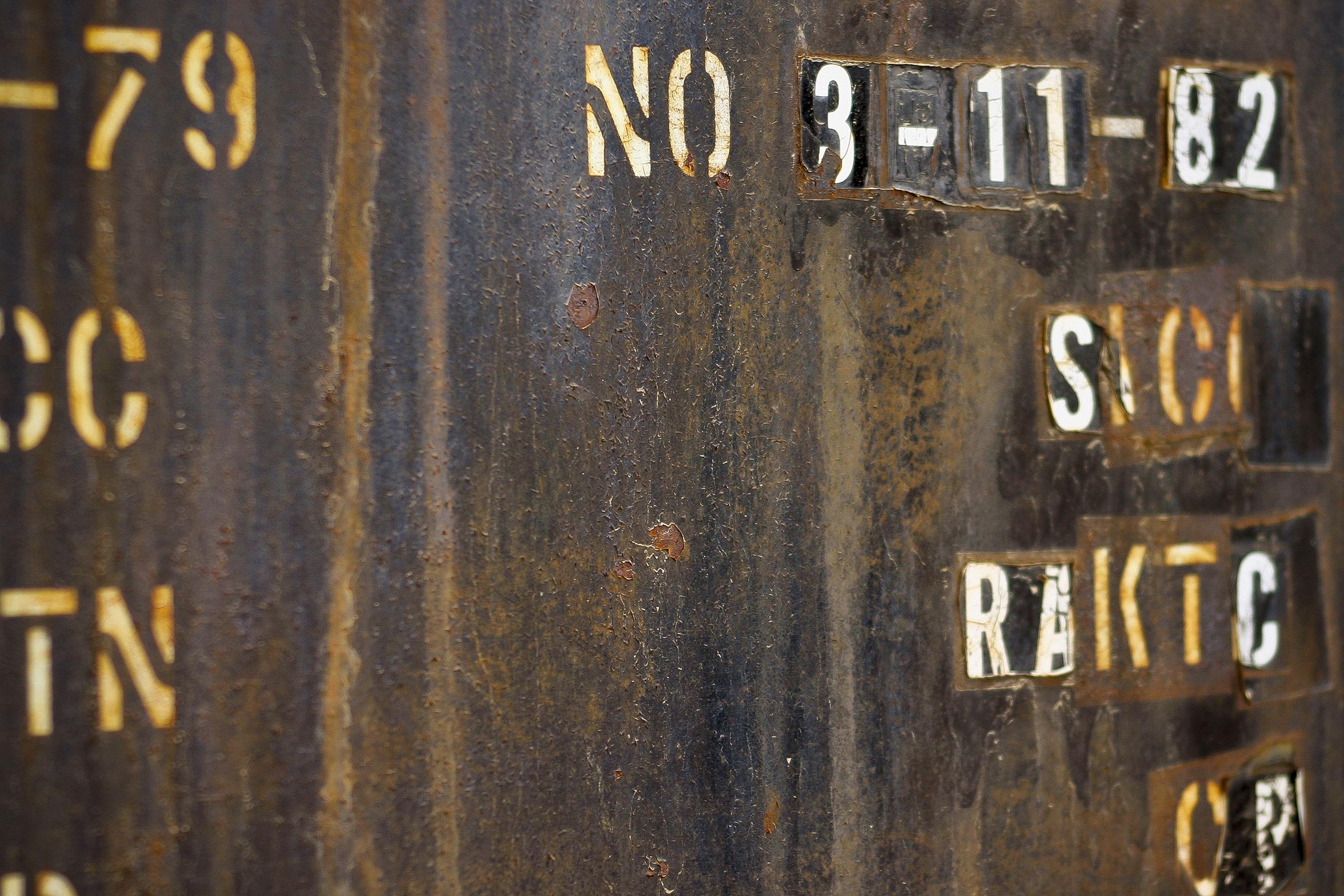Text on old rusty metal board in train