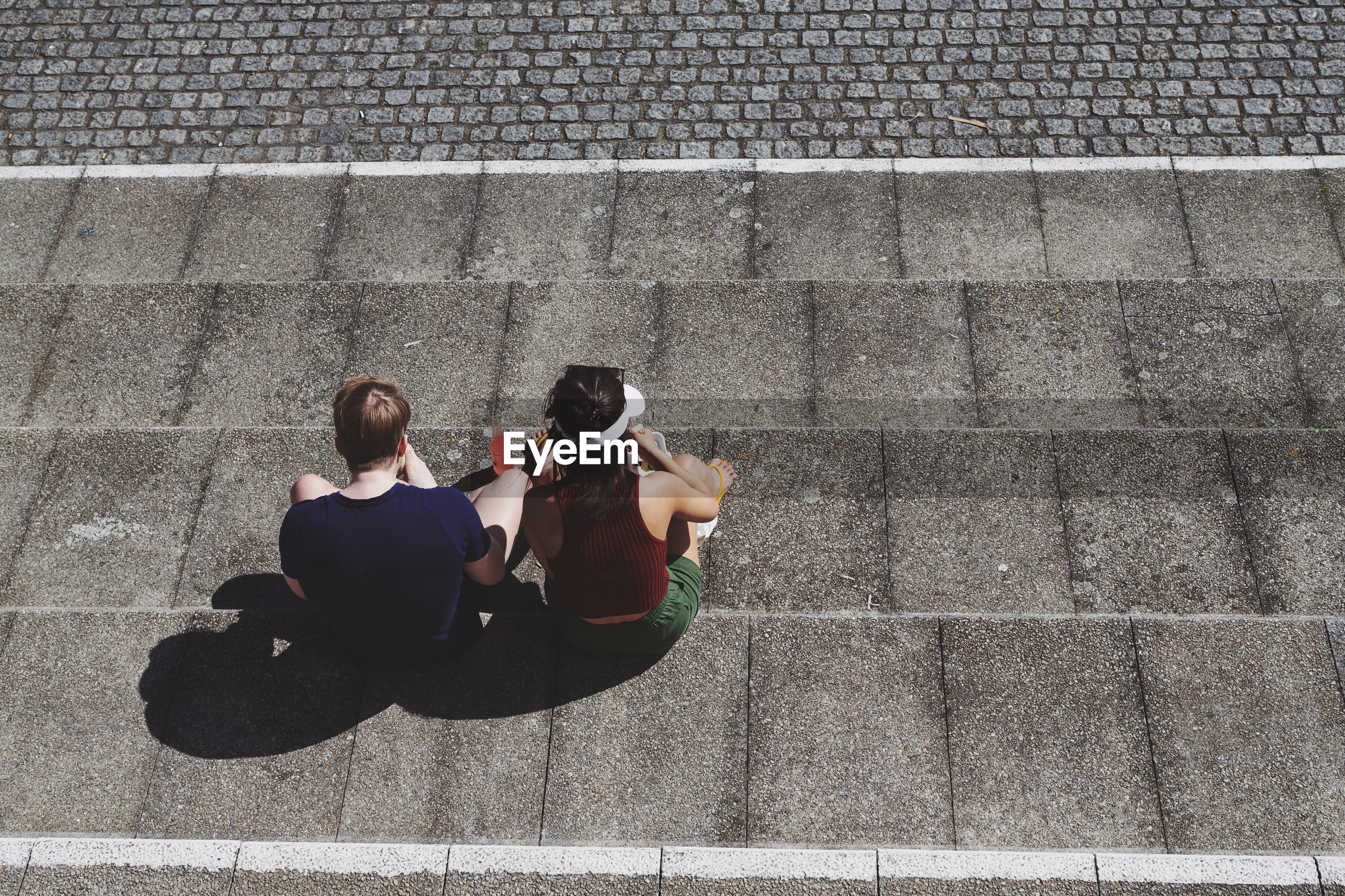HIGH ANGLE VIEW OF WOMEN SITTING ON STAIRCASE