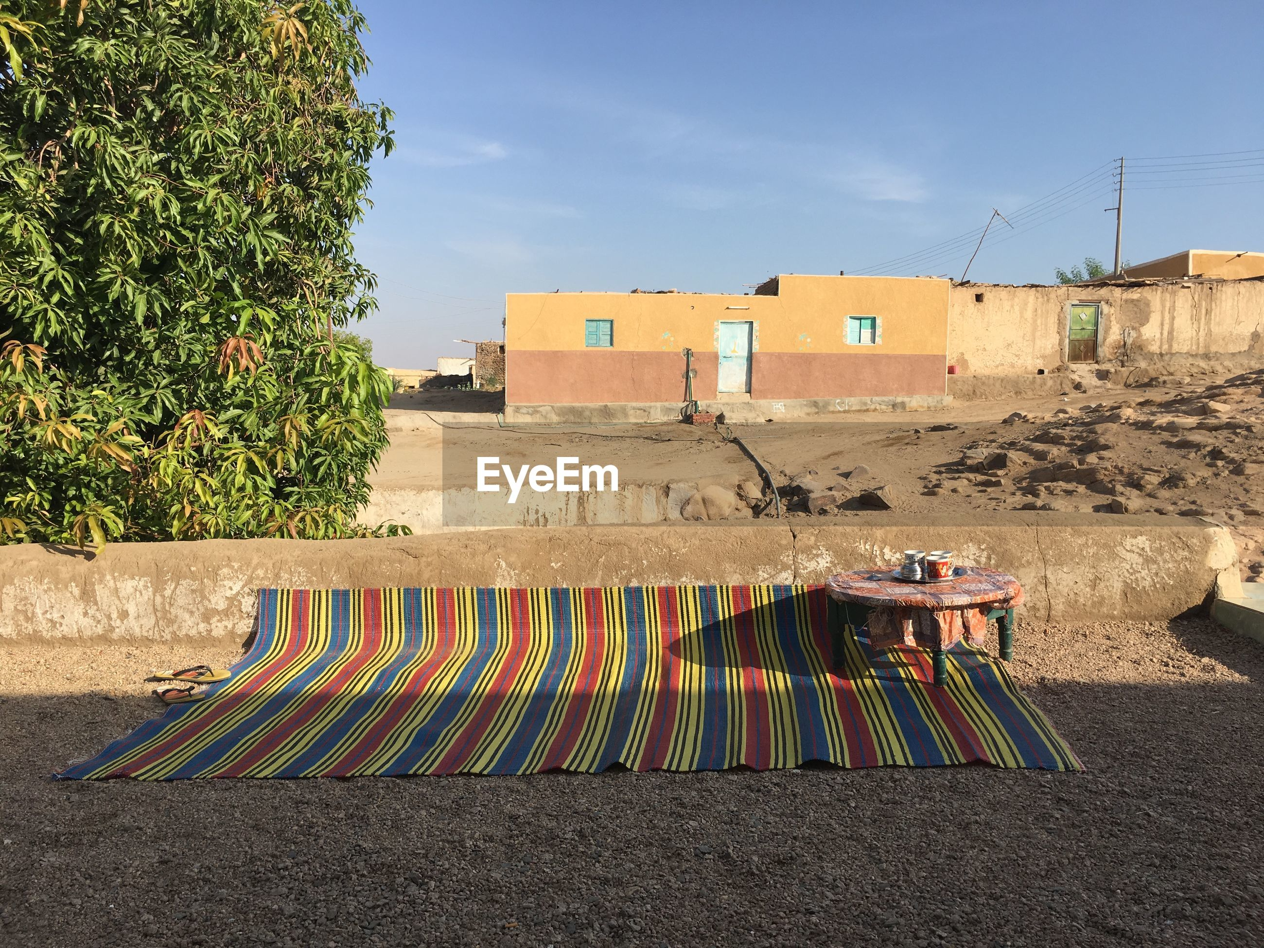 Carpet and table on field against trees and houses during sunny day
