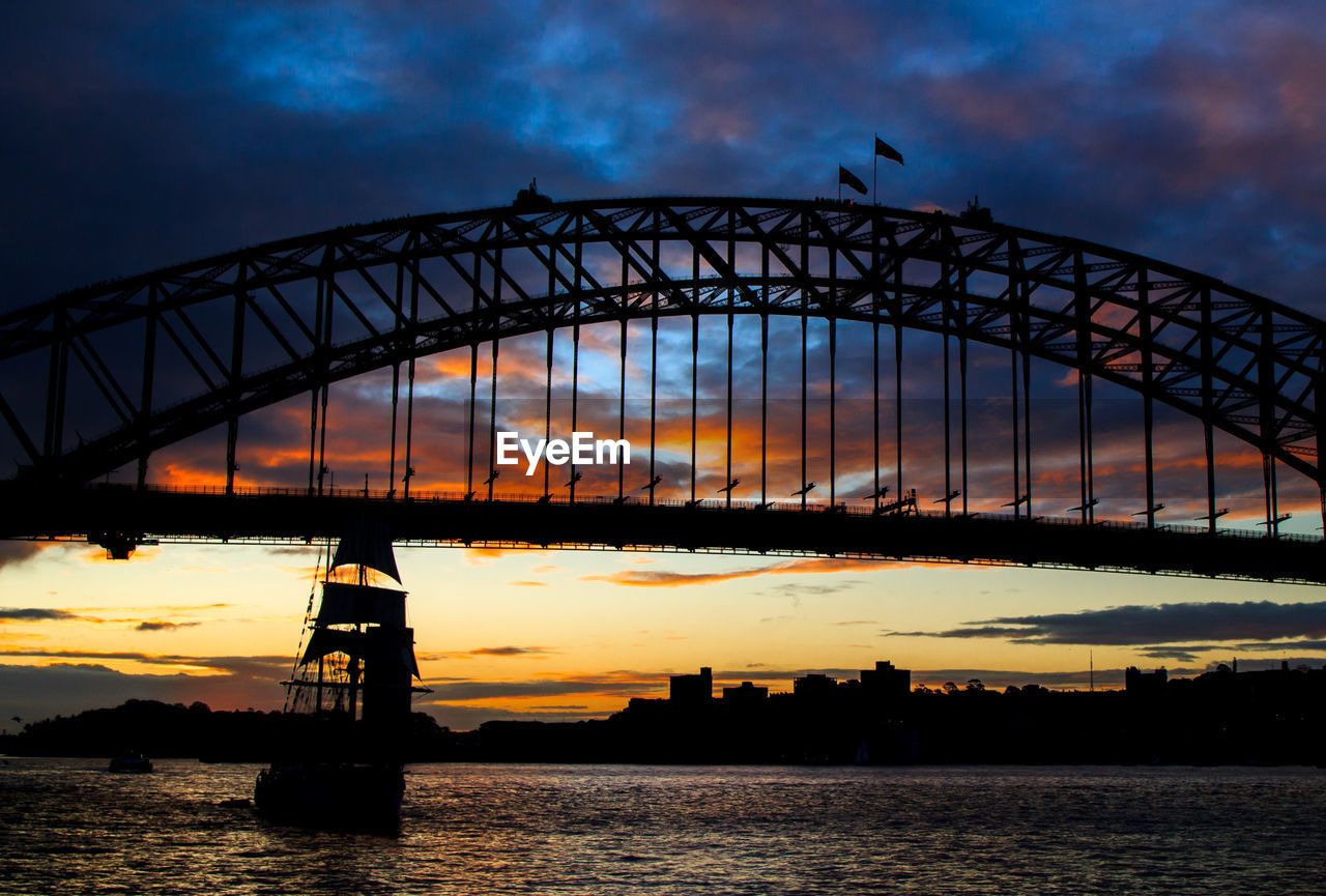 Silhouette sailing ship in bay of water against sydney harbor bridge