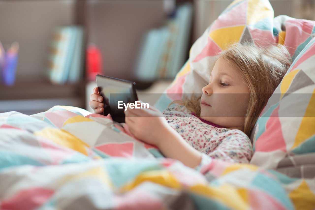 Cute girl using phone while lying on bed