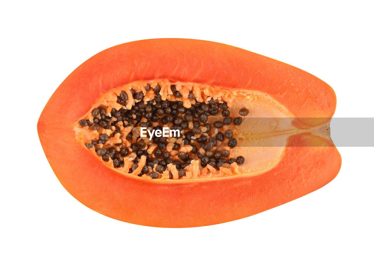 Close-up of sliced papaya over white background