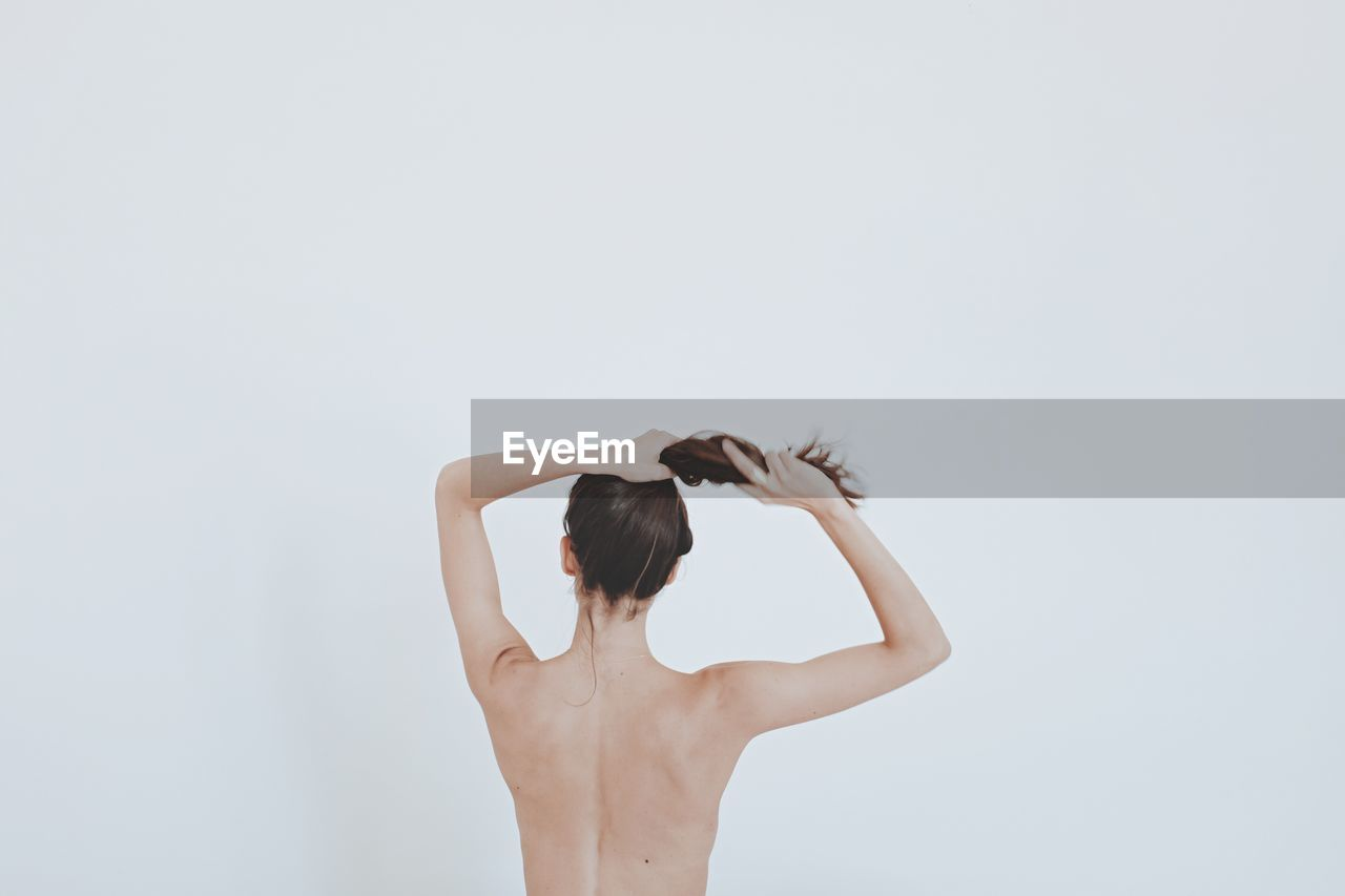 Rear View Of Young Woman Against White Background