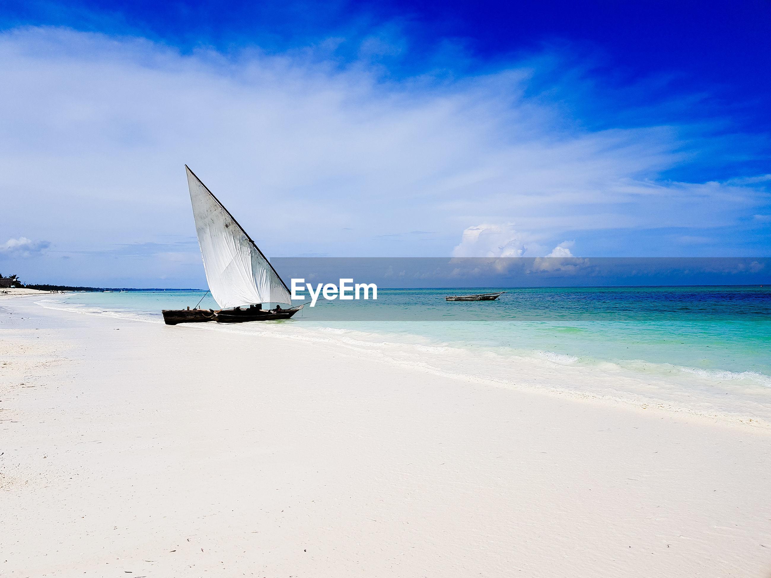 Sailboat on beach against blue sky