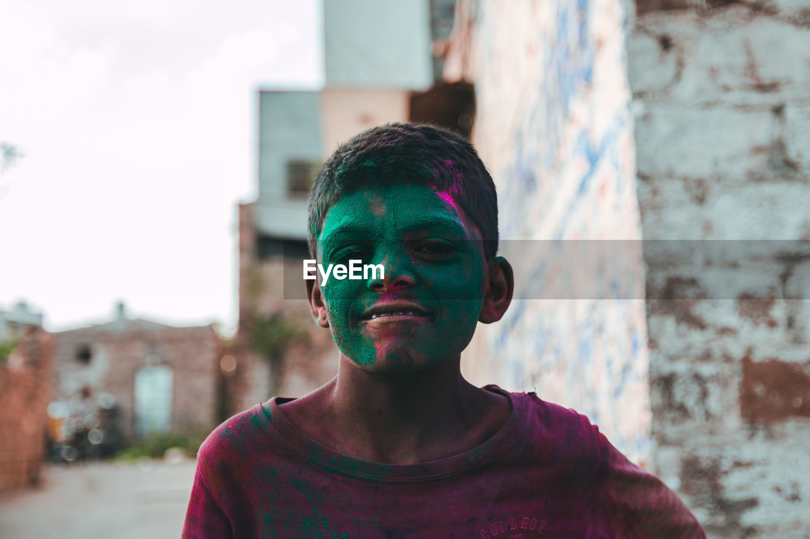 Portrait of smiling boy with green powder paint on face in town during holi