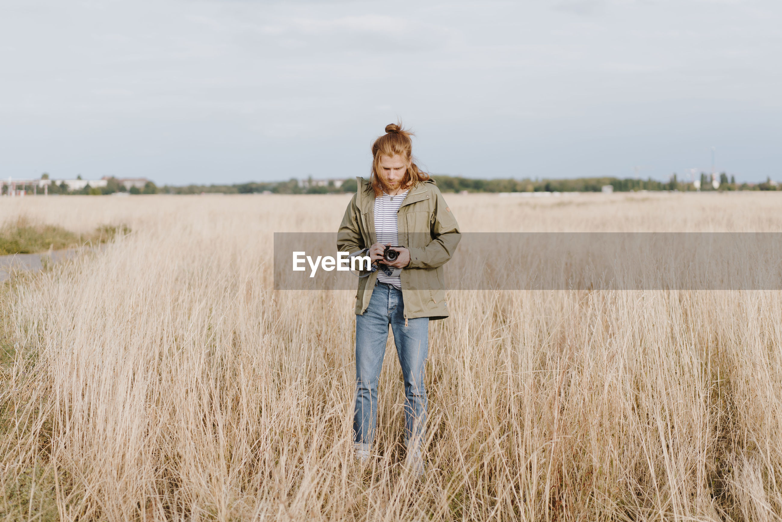 one person, land, field, standing, young adult, casual clothing, leisure activity, real people, lifestyles, plant, smiling, full length, front view, young women, sky, nature, day, happiness, hairstyle, outdoors, beautiful woman
