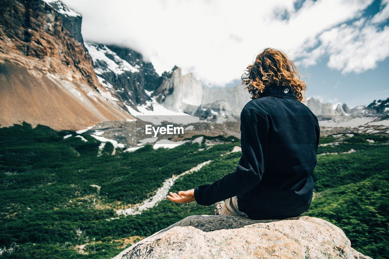 Rear View Of Woman Looking At Mountain While Sitting On Rock