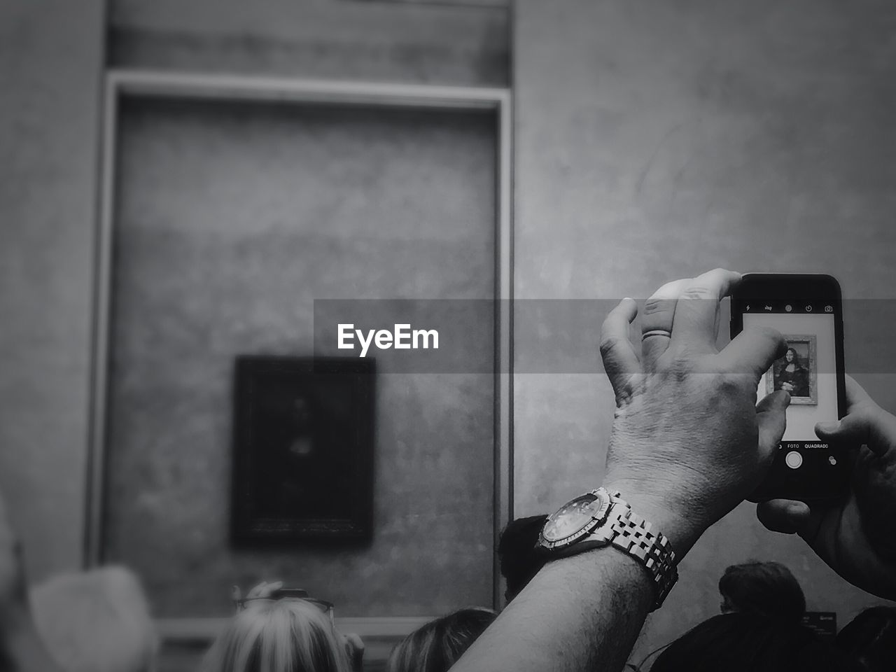 Cropped Hand Photographing Mona Lisa Painting At Museum