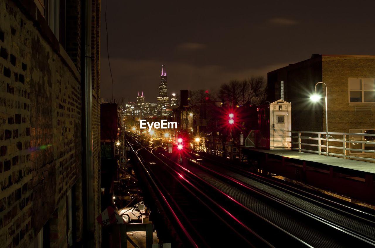 TRAIN ON ILLUMINATED RAILROAD TRACKS AGAINST SKY AT NIGHT