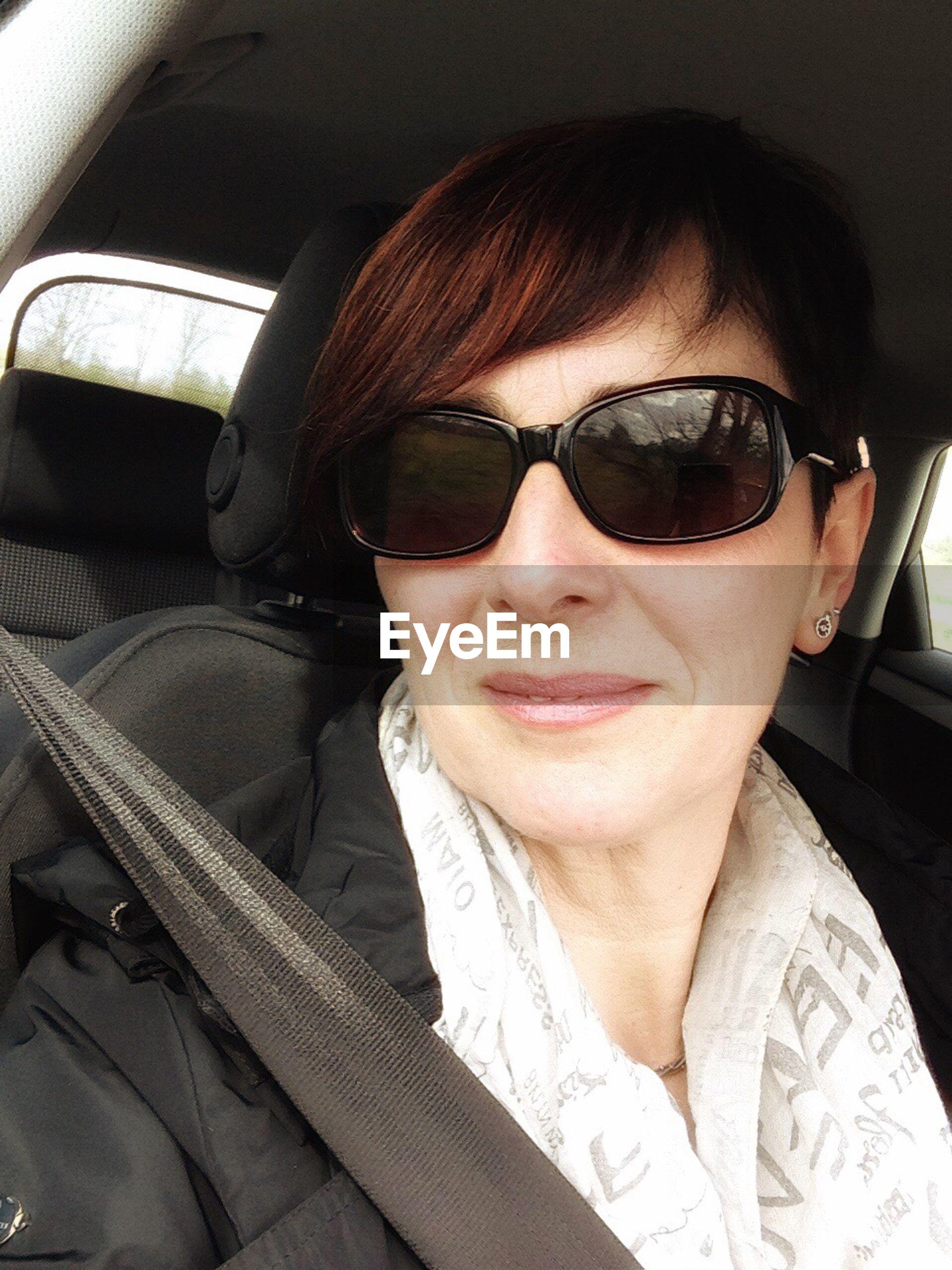 Woman wearing sunglasses driving car