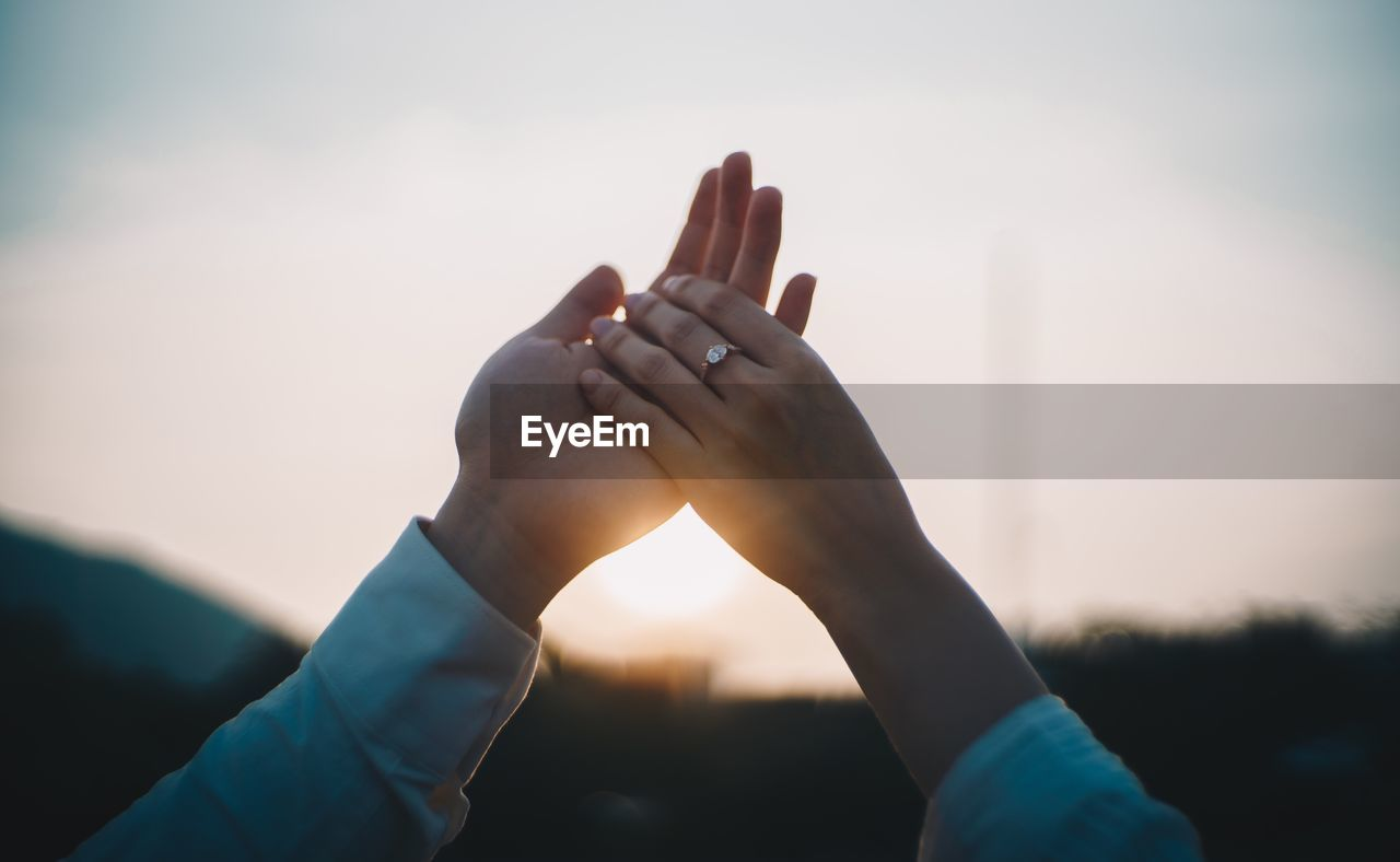 human hand, hand, human body part, real people, sky, focus on foreground, body part, one person, lifestyles, human finger, nature, finger, leisure activity, personal perspective, close-up, day, adult, sunset, sunlight, outdoors
