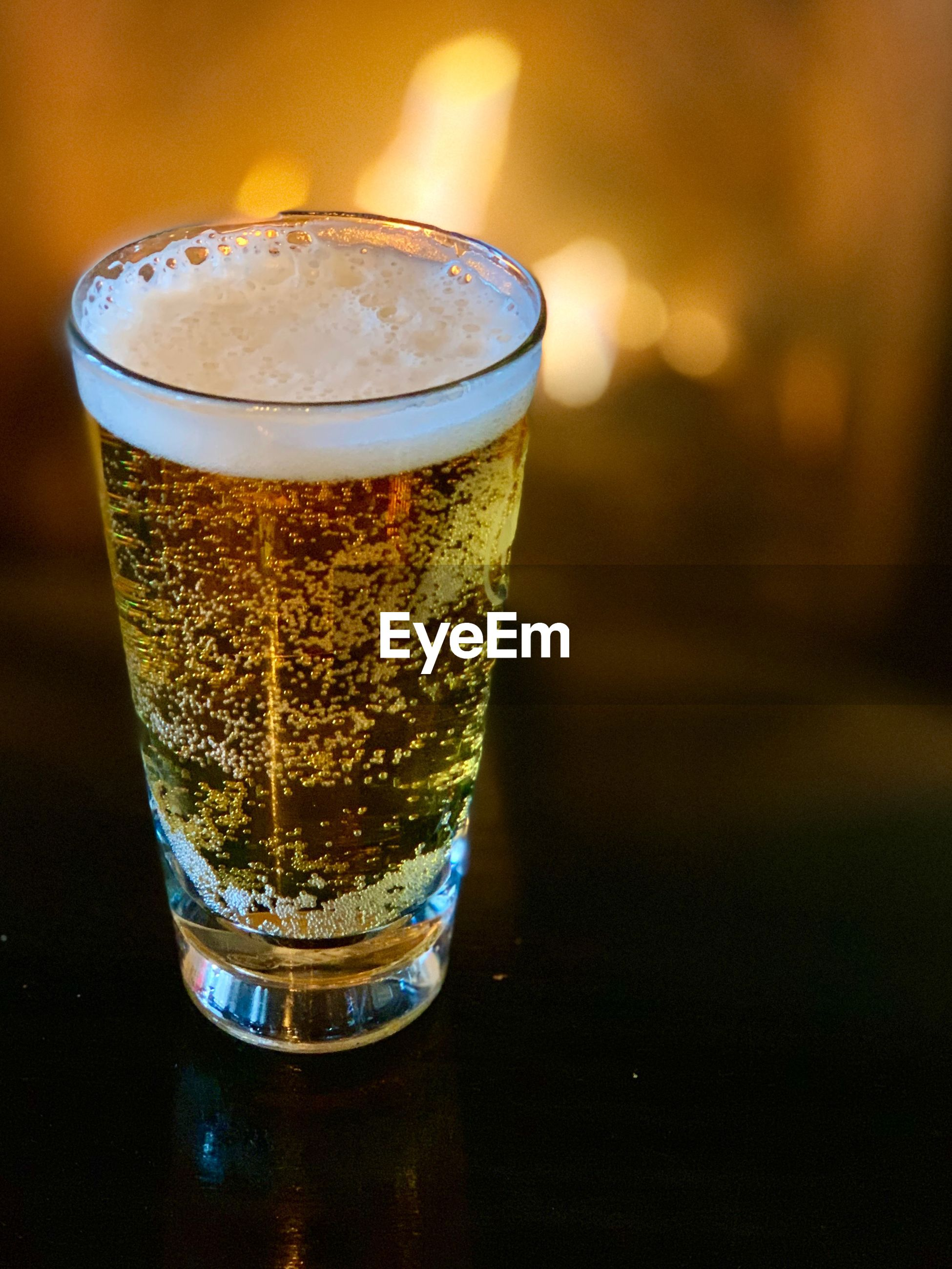 CLOSE-UP OF GLASS OF BEER ON TABLE