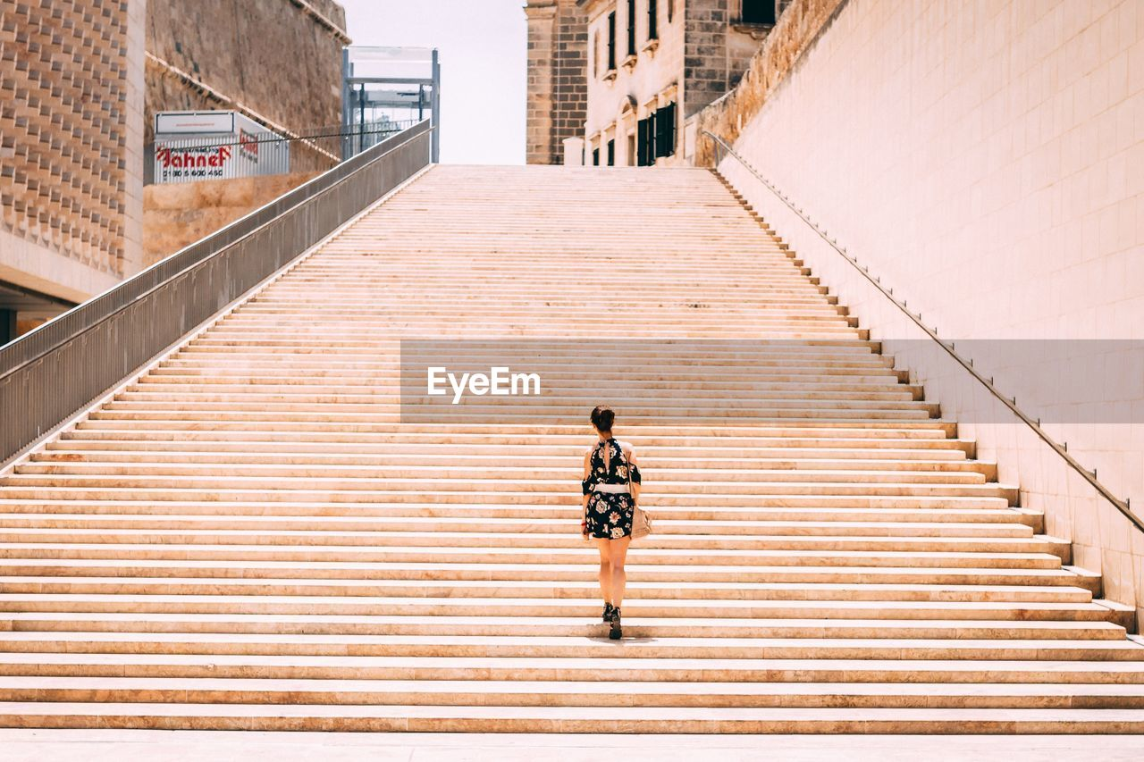 architecture, rear view, staircase, built structure, full length, one person, steps and staircases, railing, lifestyles, building exterior, walking, day, direction, the way forward, casual clothing, city, men, real people, high angle view, outdoors