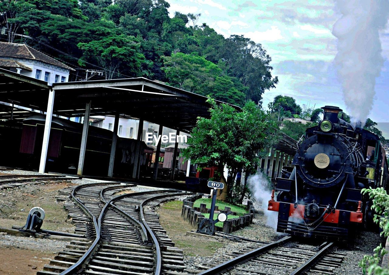 Steam train passing through railroad station platform