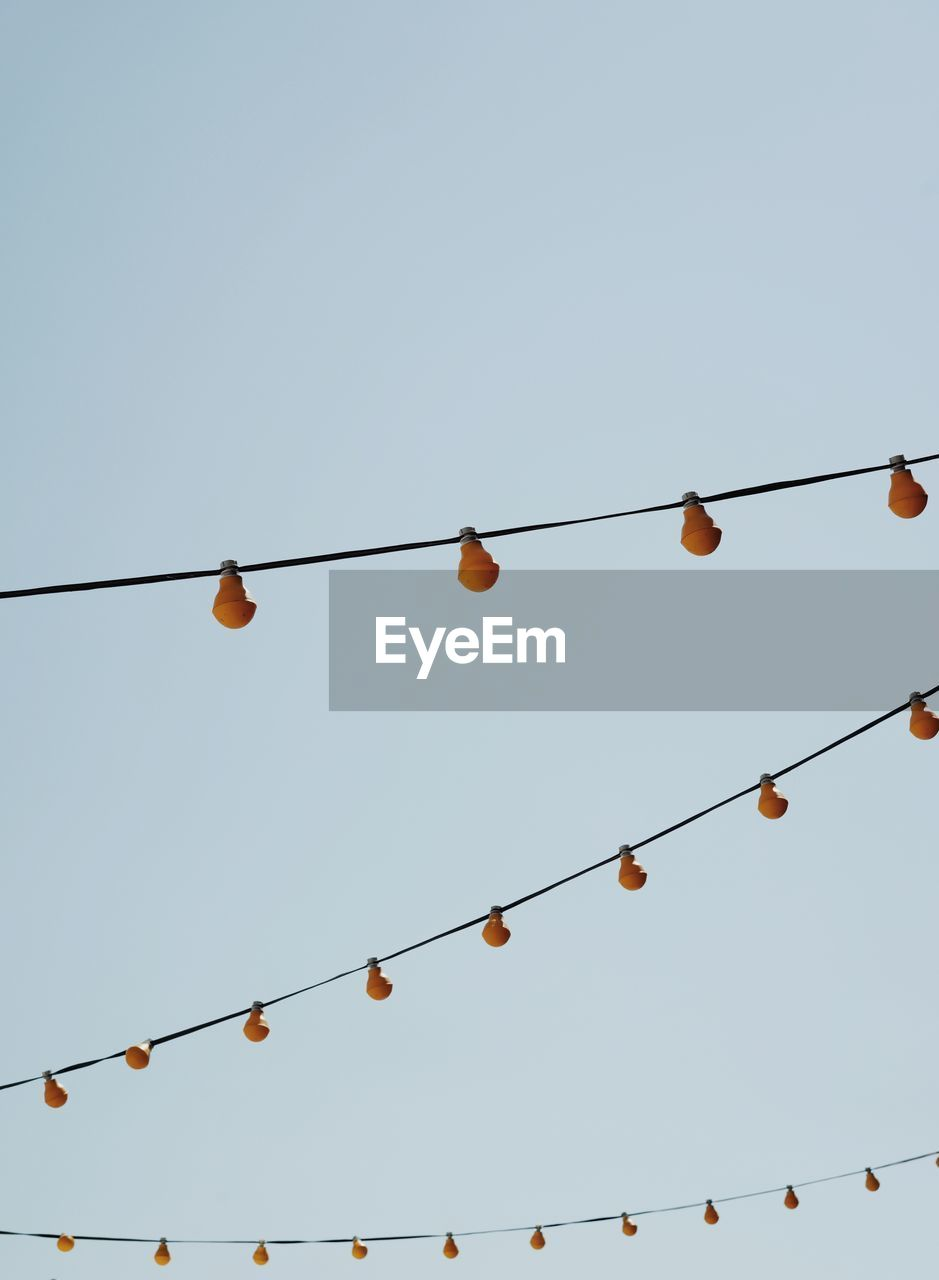low angle view, clear sky, sky, cable, hanging, light bulb, no people, copy space, nature, connection, lighting equipment, electricity, in a row, side by side, decoration, power line, day, rope, outdoors, electrical equipment