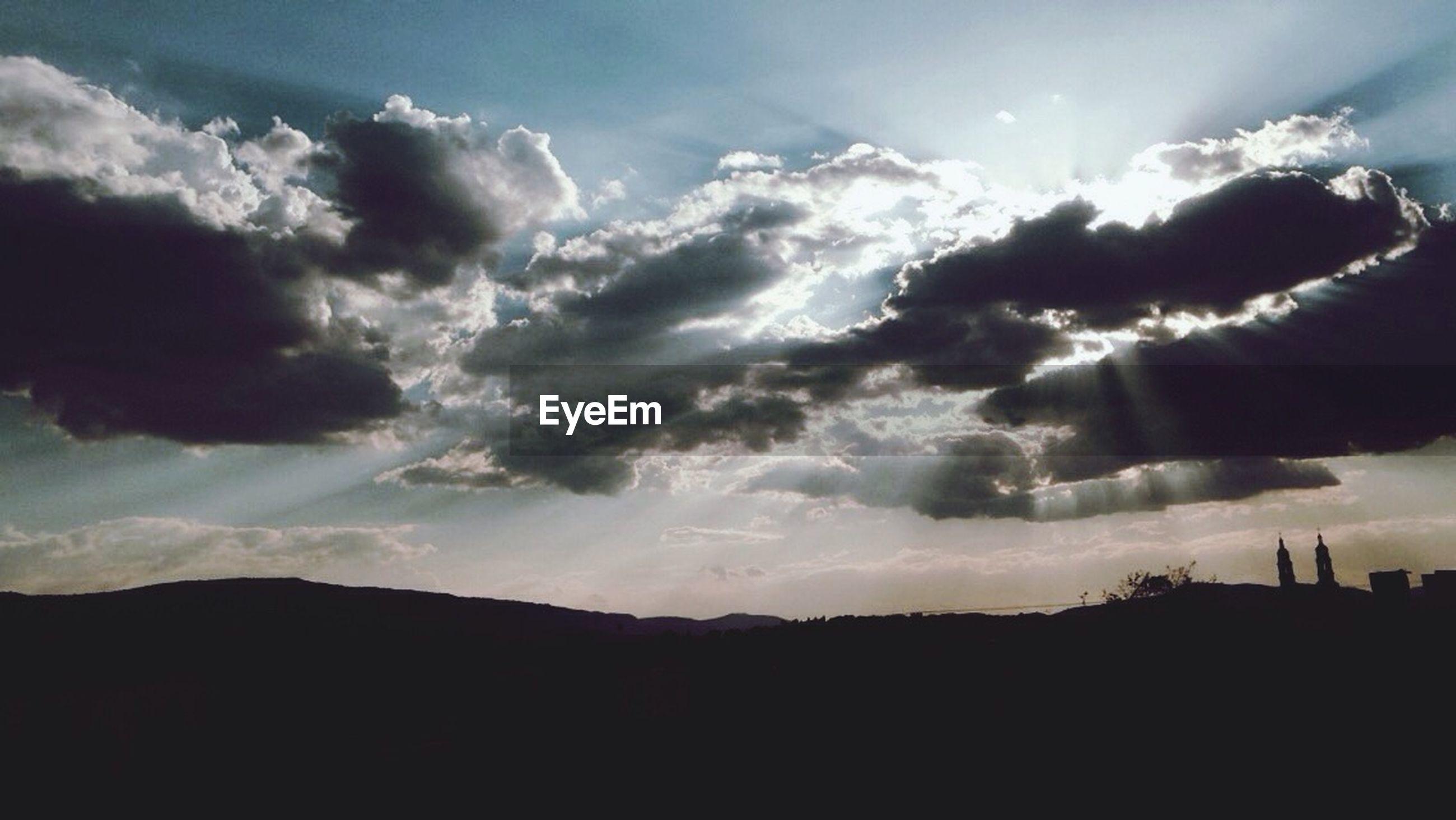 silhouette, sky, tranquil scene, scenics, tranquility, beauty in nature, cloud - sky, sunset, landscape, nature, mountain, cloud, idyllic, cloudy, sunbeam, sun, sunlight, non-urban scene, outdoors, remote