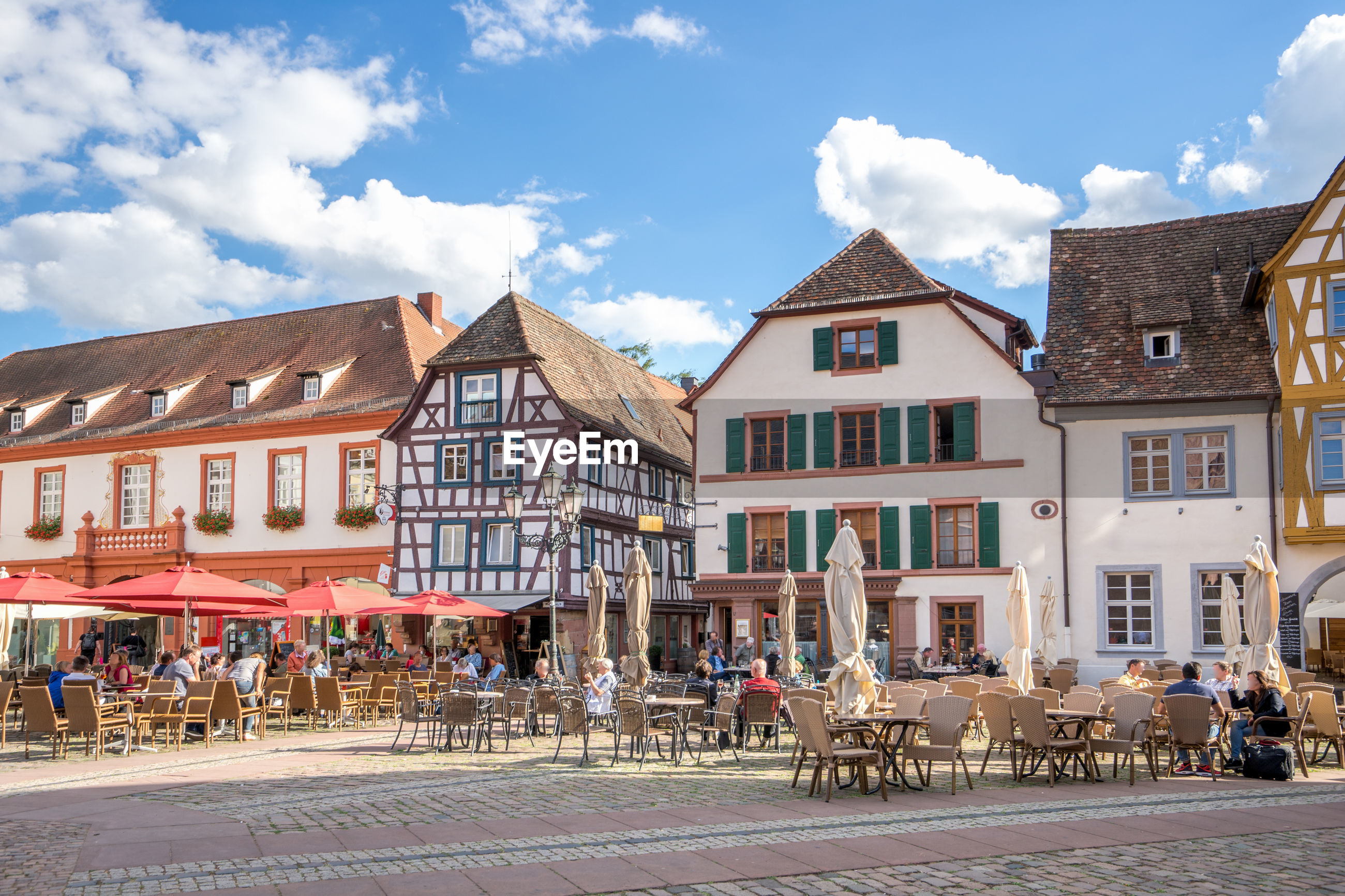 architecture, building exterior, built structure, cloud - sky, sky, city, building, nature, day, table, street, seat, chair, horse, incidental people, town, residential district, outdoors, people, town square