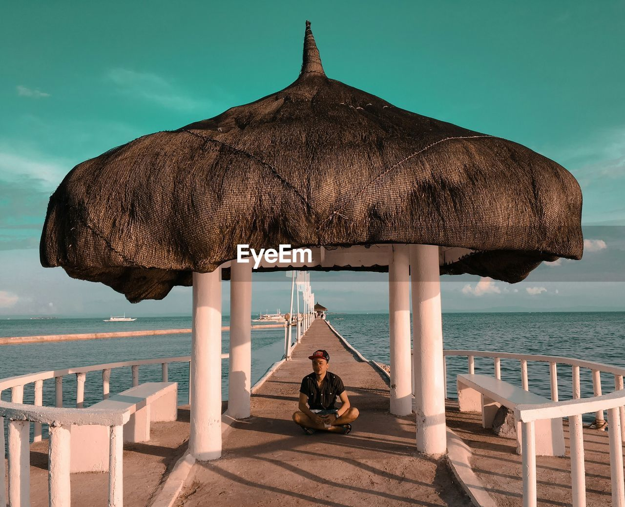 Man sitting below gazebo on pier against turquoise sky