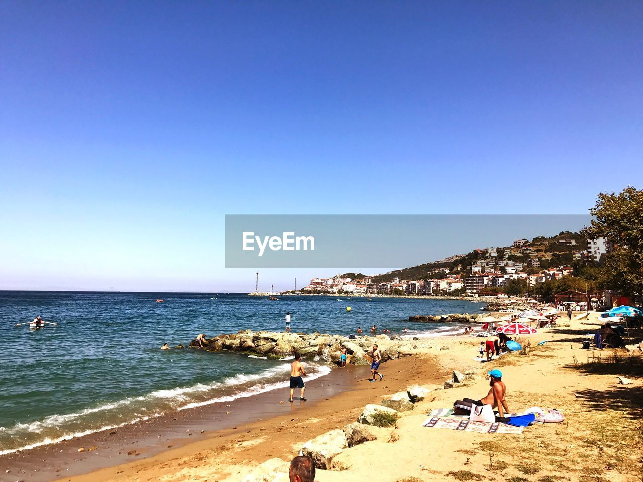 beach, sea, copy space, water, clear sky, day, blue, real people, nature, sand, outdoors, large group of people, horizon over water, summer, sunlight, men, scenics, vacations, beauty in nature, lifestyles, sky, people