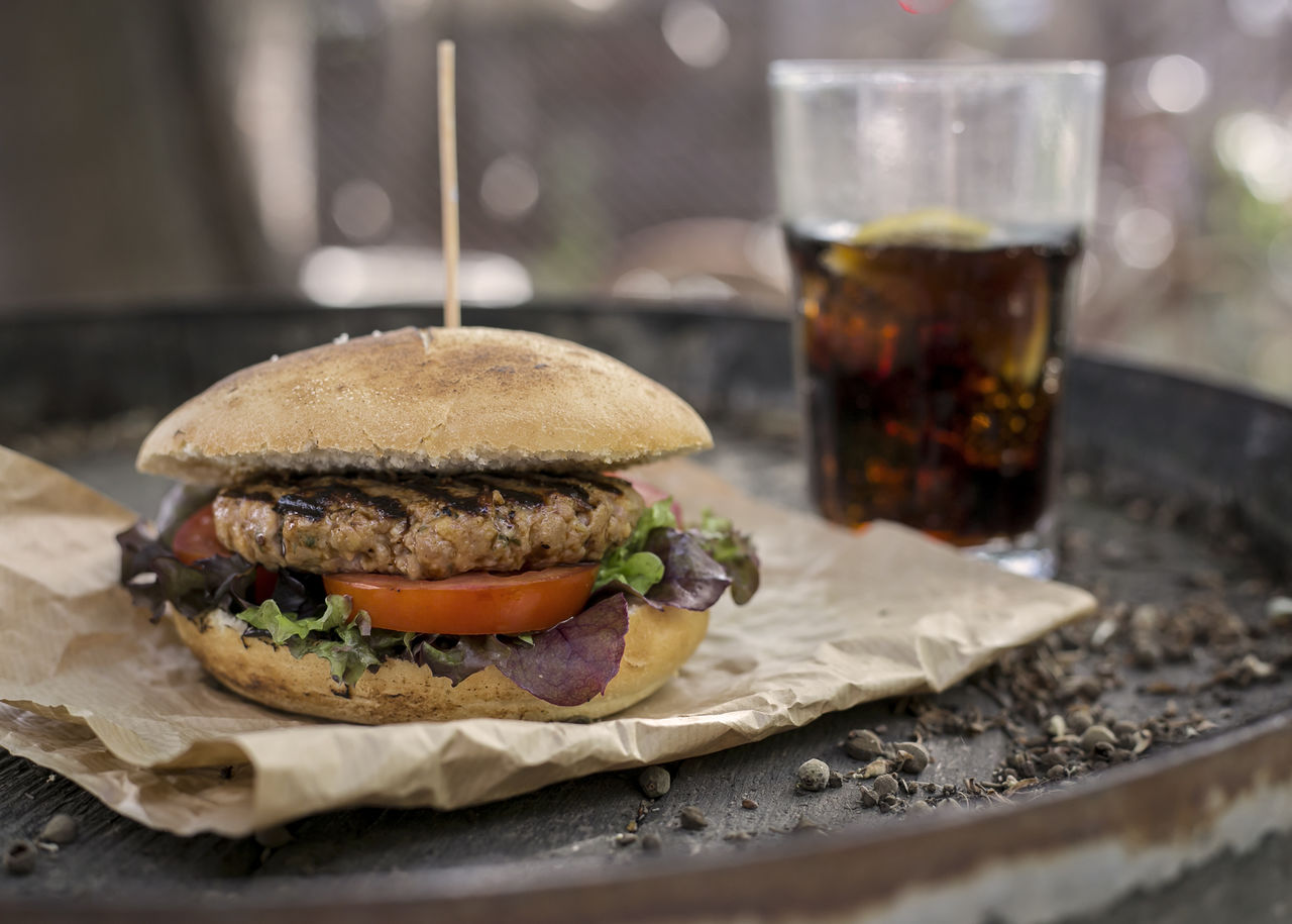 Close-Up Of Hamburger And Drink On Barrel