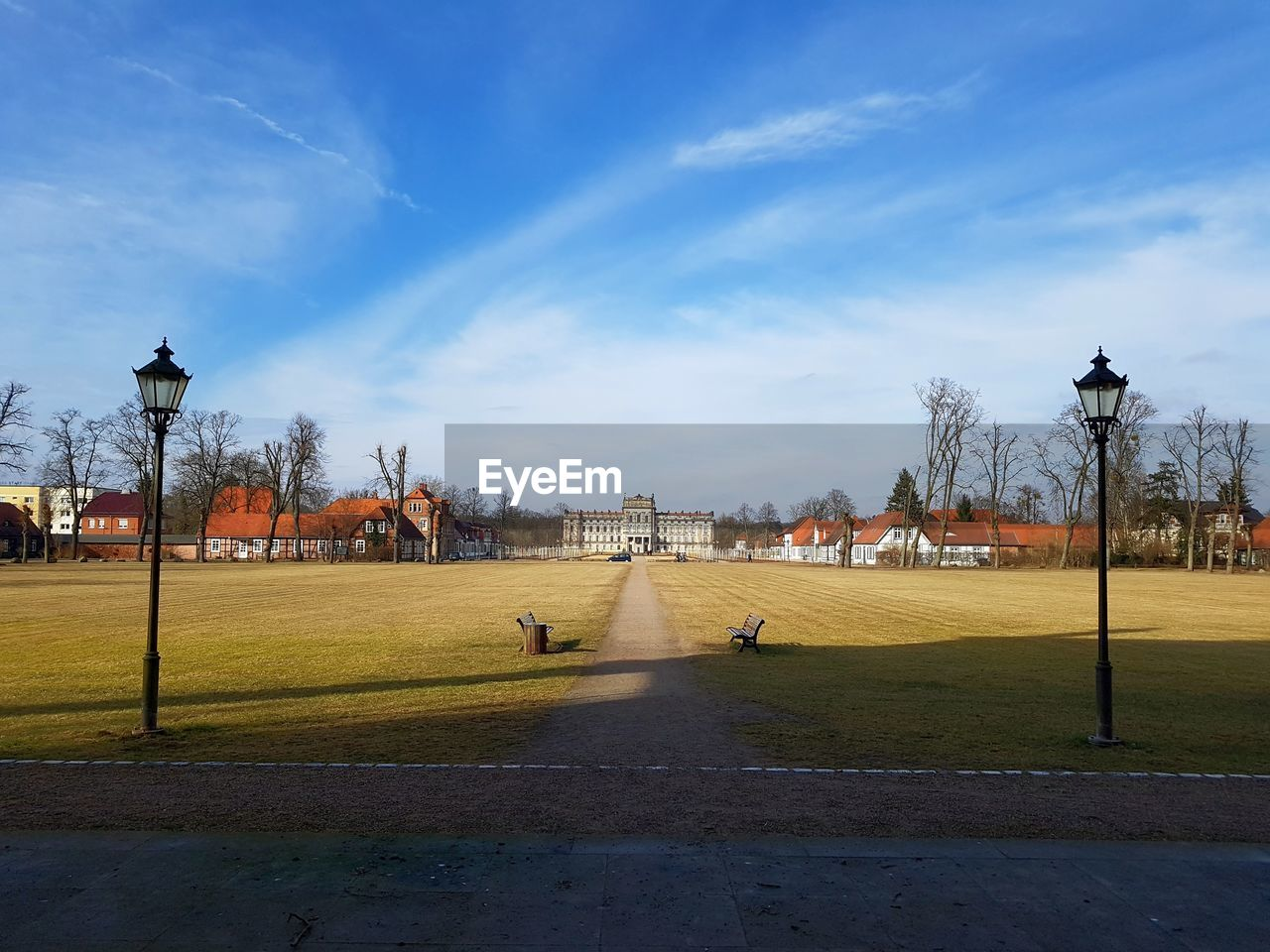 sky, street light, sport, cloud - sky, nature, architecture, building exterior, street, tree, lighting equipment, built structure, plant, day, city, grass, outdoors, sunlight, footpath, playing field, incidental people