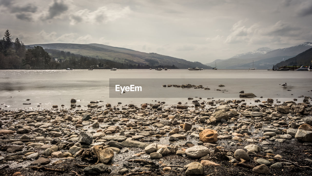 water, sky, rock, cloud - sky, mountain, solid, beauty in nature, nature, rock - object, scenics - nature, beach, tranquil scene, no people, tranquility, lake, day, mountain range, land, non-urban scene, pebble