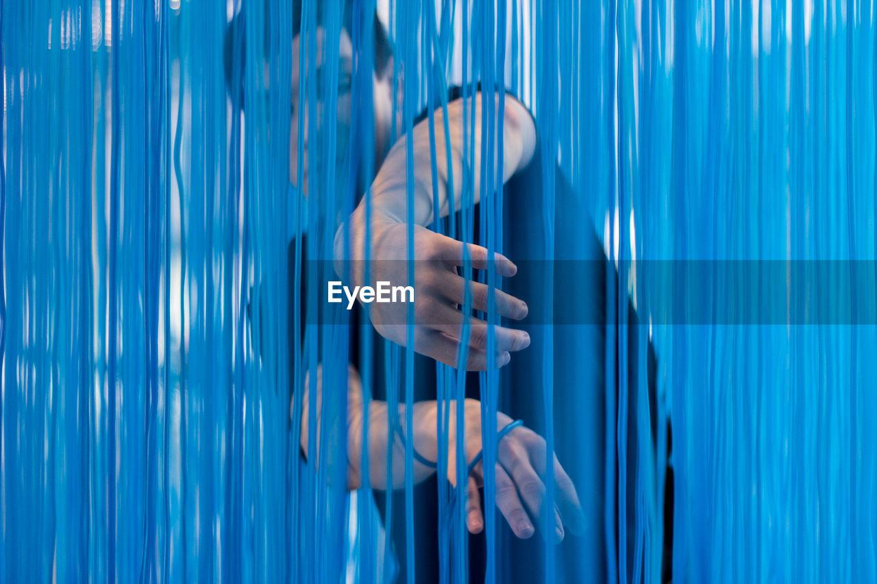 Man standing behind blue textile