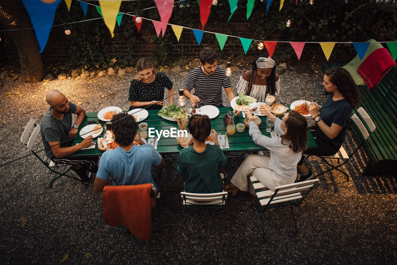 High angle view of multi-ethnic friends having food at table during dinner party in backyard