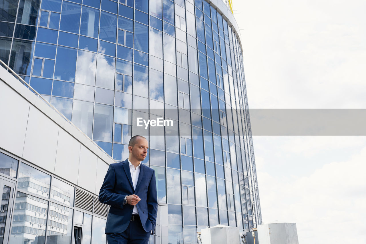 LOW ANGLE VIEW OF MAN STANDING BY MODERN BUILDING