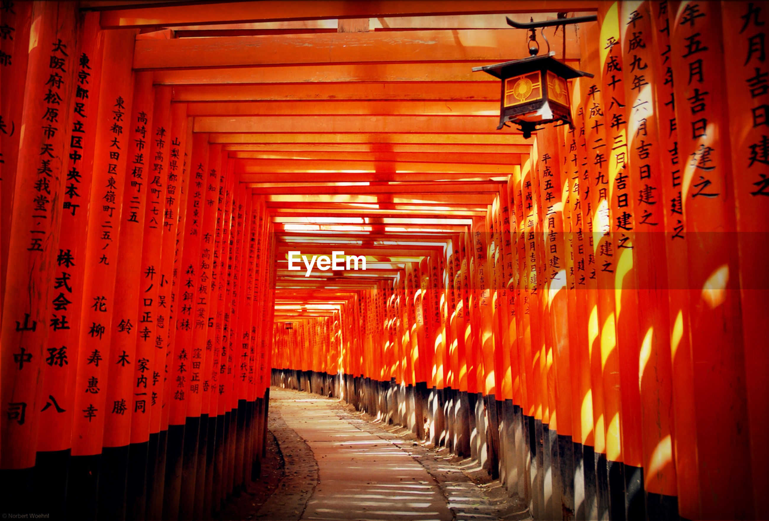 architecture, built structure, the way forward, in a row, diminishing perspective, orange color, illuminated, vanishing point, indoors, lighting equipment, architectural column, repetition, building exterior, empty, narrow, corridor, lantern, long, railing, red